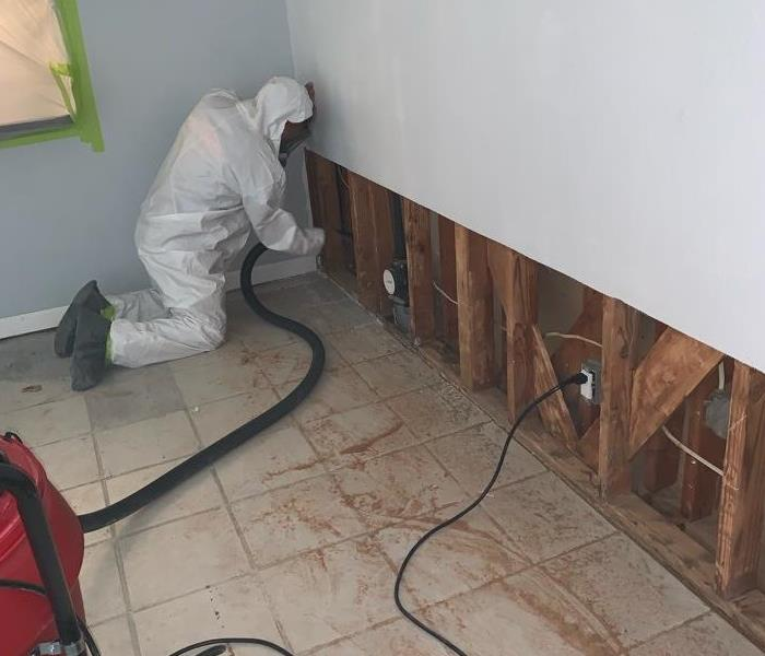 A person repairing drywall